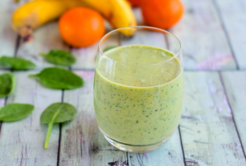 spinach banana smoothie which said good to gain weight in a glass kept on grey table
