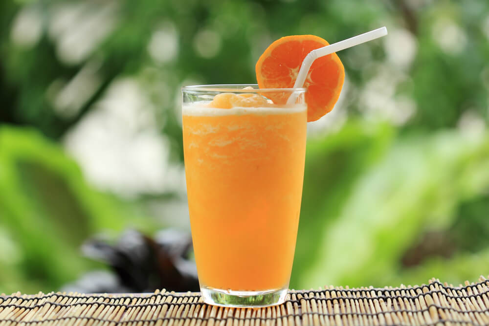 orange smoothie in a glass with a straw and orange
