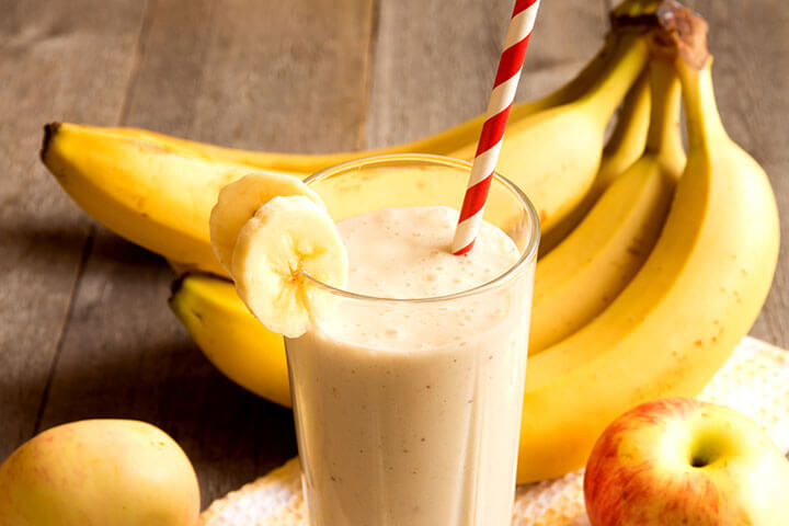 banana smoothie in a glass with straw and bananas and apple in the back