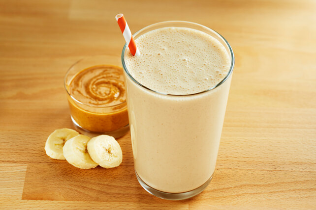 glass of peanut butter banana smoothie on brown table with banana slices and peanut butter