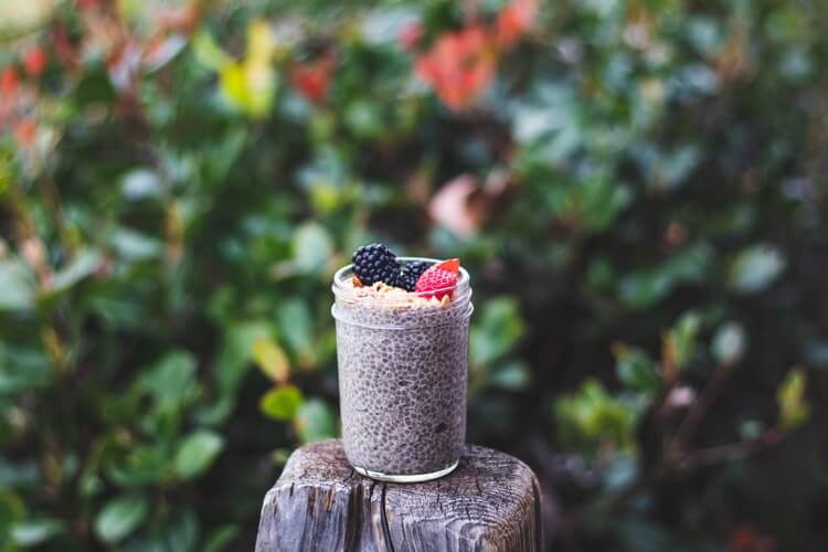 blueberry smoothie on a wood with nut and strawberries to gain weight