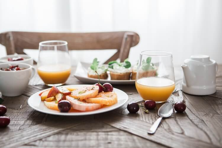 Plate of fruits with glass of juices for a healthy breakfast to lose weight