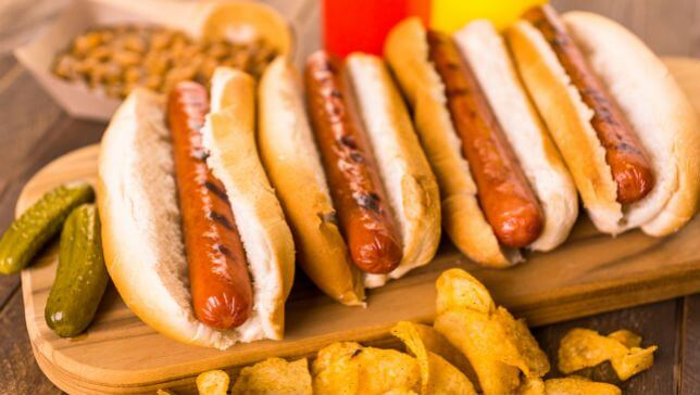 Vegan Hot Dogs with chips on a wooden board to show vegan food