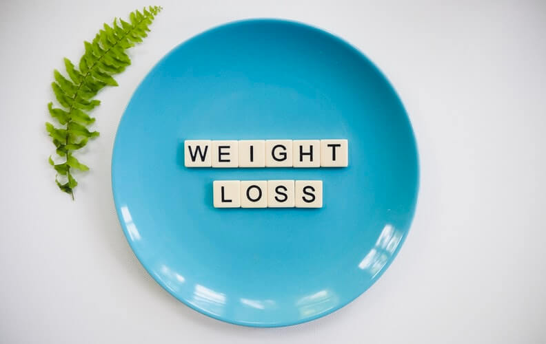 weight loss written on blue plate with a leaf