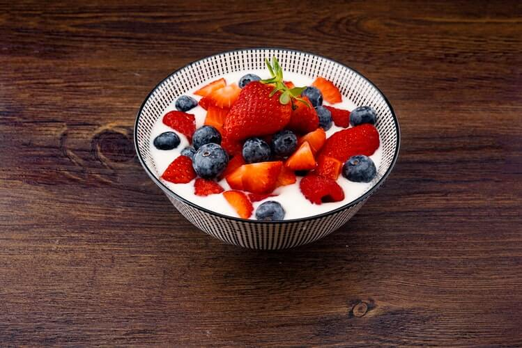 strawberry and blackberries on top of brown table
