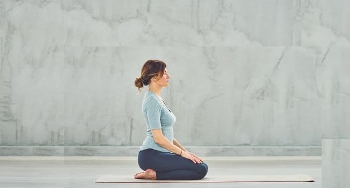 woman doing diamond pose for weight gain on a white mat