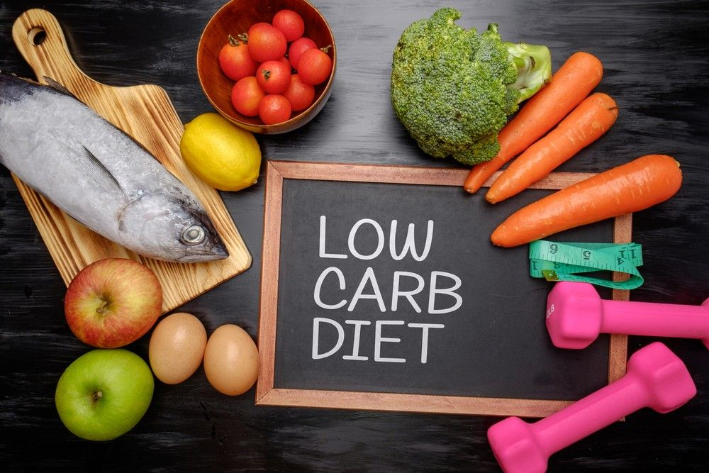 low carb diet on a board with vegetables fruits and weights kept on a table