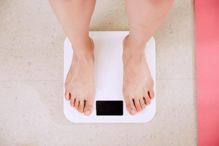 man standing on a weighing machine to show affect of a low-carb diet