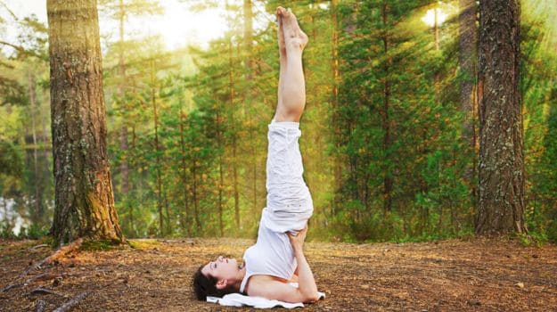 girl doing Sarvangasana Yoga for weight gain in middle of trees